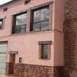 Terminación en mortero acrílico y recercos de ventanas con piedra Rodeno