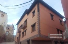 Obra nueva revestimiento de fachada con terminación en mortero monocapa con zócalo y esquinas en piedra natural.