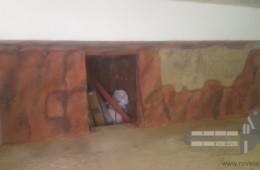 Revestimiento de entrada de bodega. Tematización en imitación rocas y piedra.