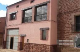 Rehabilitación de fachada con aislamiento proyectado y terminación en mortero acrílico con recercos de ventanas con piedra rodeno
